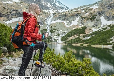 Woman hiker, hiking backpacker traveler camper walking on the top of autumn mountain in sunny day under sun light. Beautiful mountain landscape view.