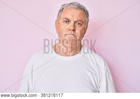 Senior grey-haired man wearing casual white tshirt with serious expression on face. simple and natural looking at the camera.