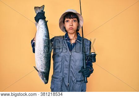 Beautiful brunettte fisher woman holding fishing rod and raw salmon puffing cheeks with funny face. mouth inflated with air, catching air.