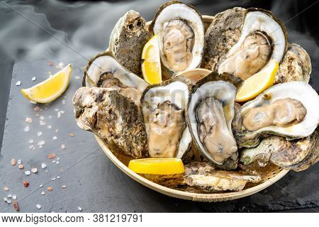 Fresh oyster serve with lemon in basket on black stone plate. Fresh seafood food and european cuisine gourmet concept.