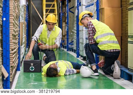 Warehouse worker do first aid to his colleague lying down on warehouse floor after accident while working. Using for industrial safety first and business insurance concept.