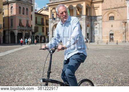 Man riding his bike in a city square
