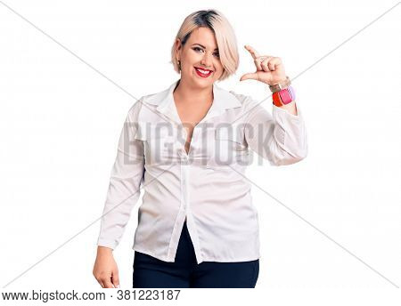 Young blonde plus size woman wearing casual shirt smiling and confident gesturing with hand doing small size sign with fingers looking and the camera. measure concept.