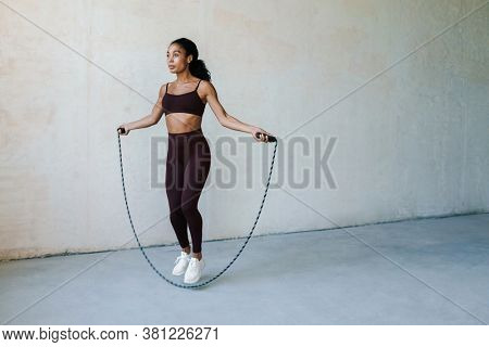 Photo of athletic african american woman doing exercise with jump rope while working out indoors