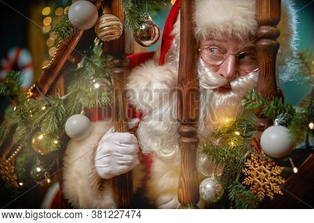 Merry Christmas and Happy New Year! Close-up portrait of  jolly Santa Claus peeking over the banister on the stairs in a beautiful New Year's interior.