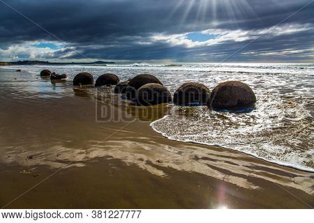 The concept of exotic and ecological tourism. The South Island of New Zealand. Popular tourist attraction. Moeraki Boulders is the group of large spherical boulders. Low tide in the Pacific ocean