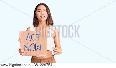 Young beautiful chinese girl holding act now banner smiling happy pointing with hand and finger