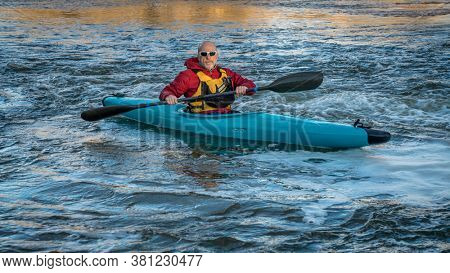 senior male paddling a whitewater kayak on a turbulent river - South Platte River in northern Colorado, fitness and recreation concept
