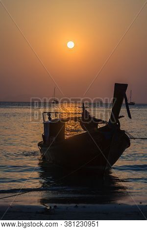 Sunset Over The Sea With Boat Silhouette