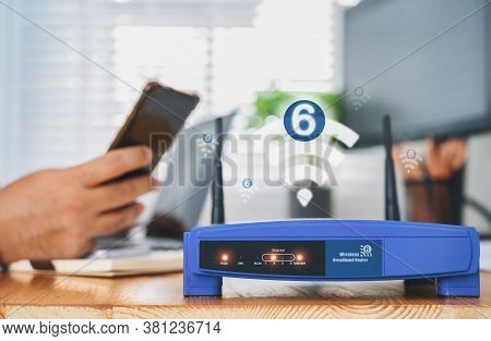 Closeup Of A Wireless Router With Wifi 6 Technology And A Man Using Smartphone On Living Room At Hom