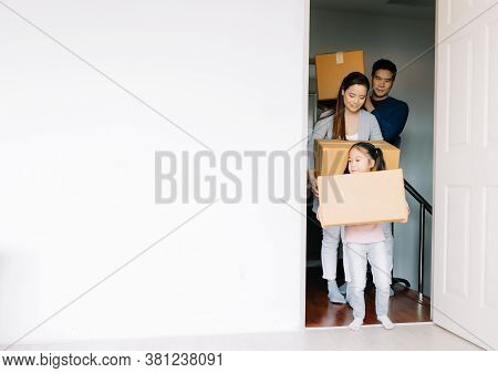 Happy Young Asian Family With Cute Daughter Carrying Boxes Into The A New Home On Moving Day. Moving