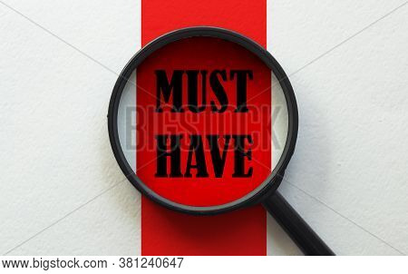 Magnifier With Text Must Have On The White And Red Background