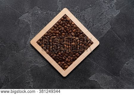 Coffee beans in wooden box on a dark surface.