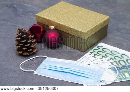 The Photo Shows A Golden Gift Box With Christmas Bauble, Pine Cones, Money And Face Mask