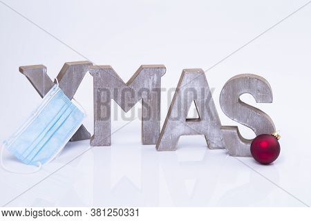 The Photo Shows The Word X-mas Written With Wooden Letters With Protective Mask And Christmas Ball
