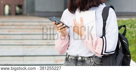 A Female Student With A Black Backpack Holds A Smartphone And Notepad On The Threshold Of The Univer
