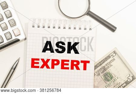 Text Ask Expert Written On Notepad With Calculator, Pensil, Magnifier And Dollars. Business Concept