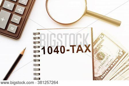 1040-tax Financial Forms With Pen And Calculator And Magnifier And Dollars On White Background