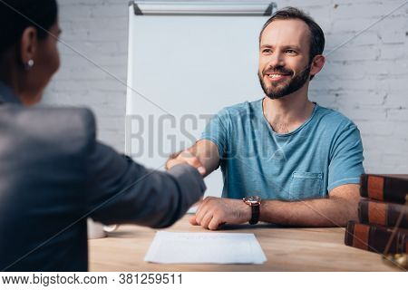 Selective Focus Of Bearded Client Shaking Hands With Lawyer