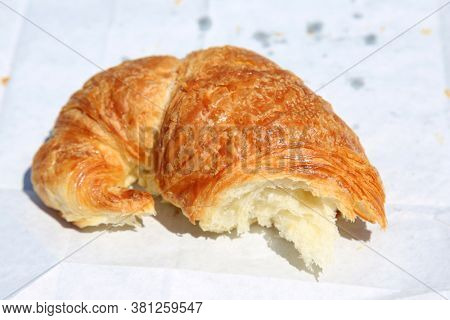 Croissant. Butter Croissant. Section of a  Fresh Baked Croissant on white paper.