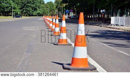 Bright Orange Traffic Cones Standing In A Row On Asphalt
