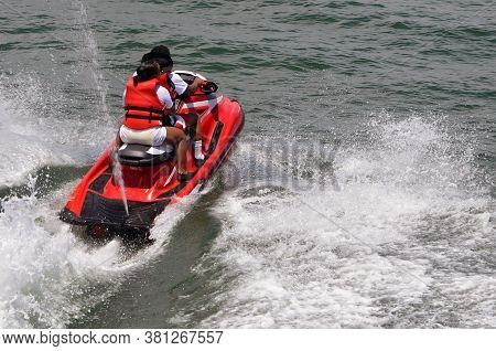 Yung Afro-american Couple Riding Tandem On A Speeding Red Jetski.