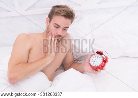 Sleepy Time. Sleepy Man Hold Clock In Bed. Unshaven Guy With Sexy Chest. Early Morning Time. Awakeni