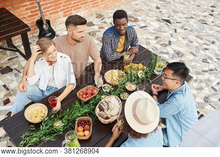 High Angle View At Multi-ethnic Group Of Young People Enjoying Dinner Outdoors, Copy Space