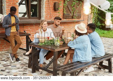 Full Length View At Multi-ethnic Group Of Young People Enjoying Dinner Outdoors, Copy Space