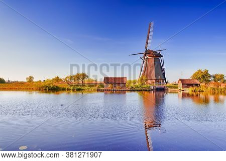 Netherlands Traveling. Traditional Dutch Windmill And Dutch Houses In Kinderdijk Village In The Neth