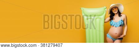 Horizontal Image Of Pregnant Woman Touching Belly While Standing With Inflatable Mattress On Yellow