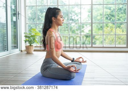 Young Asian Woman Doing Yoga Exercises At Home, Sitting In Easy With Meditating, Breathing And Relax