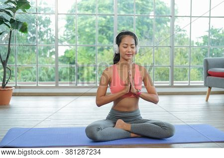 Young Asian Woman Doing Yoga Exercises At Home, Sitting In Easy With Palms In Namaste, Meditating, B