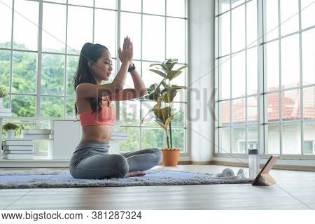 Training At Home. Young Asian Woman Doing Yoga Exercises With Palms In Namaste, Meditating, Breathin