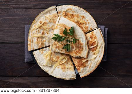 Pieces Of Quesadilla With Mushrooms Sour Cream And Cheese On A Plate With Parsley Leaves. Wooden Bac