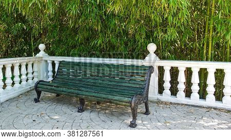 In A Shady Corner Of The Park, There Is A Green Wooden Bench With Metal Curly Legs. Nearby Is A Whit