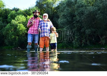 Boy With Father And Grandfather Fly Fishing Outdoor Over River Background. Fishing. Father, Son And