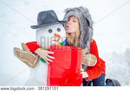Funny Snowmen. Happy Smiling Girl Kissing Snowman On Sunny Winter Day. People Love Winter. Snowman.