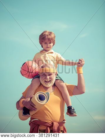 Joyful Old-aged Man And Cute Little Boy Practicing Sport And Healthy Lifestyle Over Sky Background.