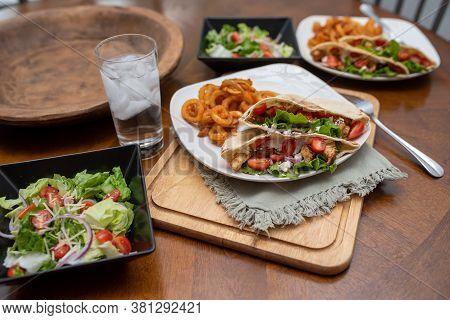 Chicken Souvlaki Pita With Tzatziki, Greek Style Sandwich Served With Salad And Curly Fries.