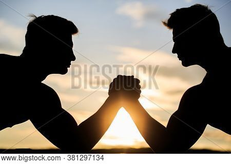 Silhouette Of Hands That Compete In Strength. Rivalry, Closeup Of Male Arm Wrestling. Men Measuring