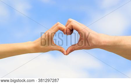 Heart From Hands On A Sky Background. Love, Friendship Concept. Girl And Male Hand In Heart Form Lov