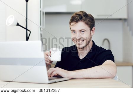 Smiling Young Man Working At Home On Laptop Sitting At Desk And Holding A Cup Of Coffee. Work At A D