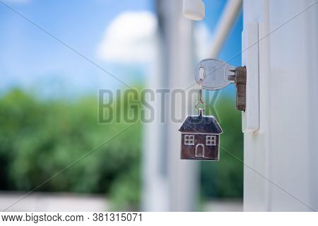 The House Key For Unlocking A New House Is Plugged Into The Door. Concept Of Rented House , Buy Or S