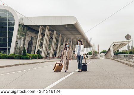 Two Young Women With Suitcases Return From A Business Trip During Quarantine. Women With Protective