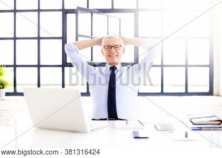 Shot Of Relaxed Businessman With Hands On His Hand Sitting Behind His Laptop At Office Desk While Lo