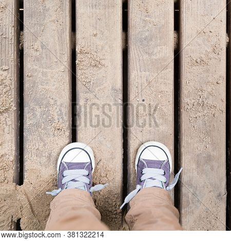 The Kid Stands On A Wooden Bridge In The Playground. Top View On The Feet Of A Child In Sportswear A