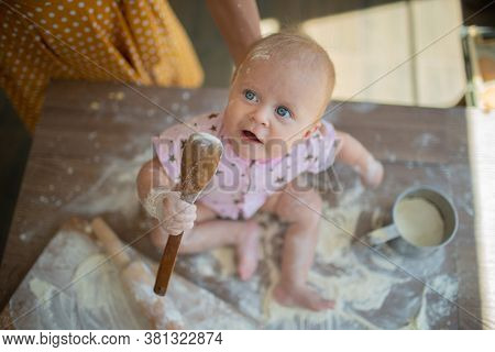 Woman mother with little toddler in the kitchen cook from flour and have fun having fun