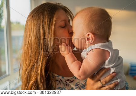 Portrait of a woman mother with a newborn baby in her arms at home next to a window in the room