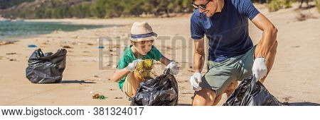 Dad And Son In Gloves Cleaning Up The Beach Pick Up Plastic Bags That Pollute Sea. Natural Education